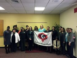 Various members of the Women's Center holding up the Women's History Month Flag.