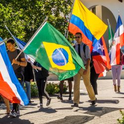Phtoto of students carrying flags from around the world
