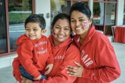 Woman holding child smiling next to another woman, all wearing Montclair State University hooded sweatshirts.