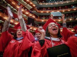Photo of celebrating graduate students at commencement ceremony in red robes.
