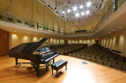 photo of piano on stage in an empty recital hall