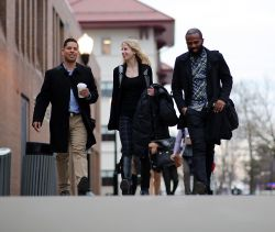 Group of three graduate students in business clothes walking on campus.
