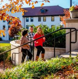 Group of three undergraduate students walking up steps on campus on sunny Fall day.