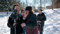 Student film crew making a movie on campus in winter