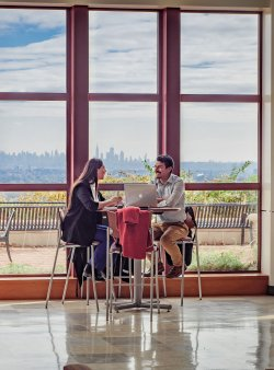 Students in front of window overlooking NYC skyline