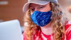 Woman wearing face mask using laptop