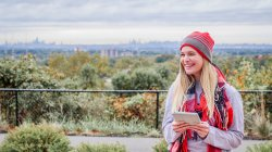 female student in winter clothes on campus with view overlooking NYC skyline