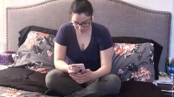 Student sitting on her bed at home texting