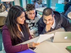 Photo of three students writing and collaborating in the library with a paper and a laptop.