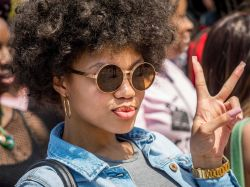 Photo of student on campus wearing sun glasses and displaying a peace sign.