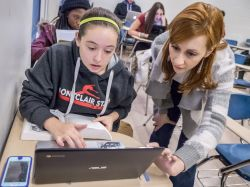 Photo of faculty member and student looking at a laptop in collaboration.