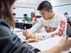 photo of student at desk writing wearing Montclair State shirt