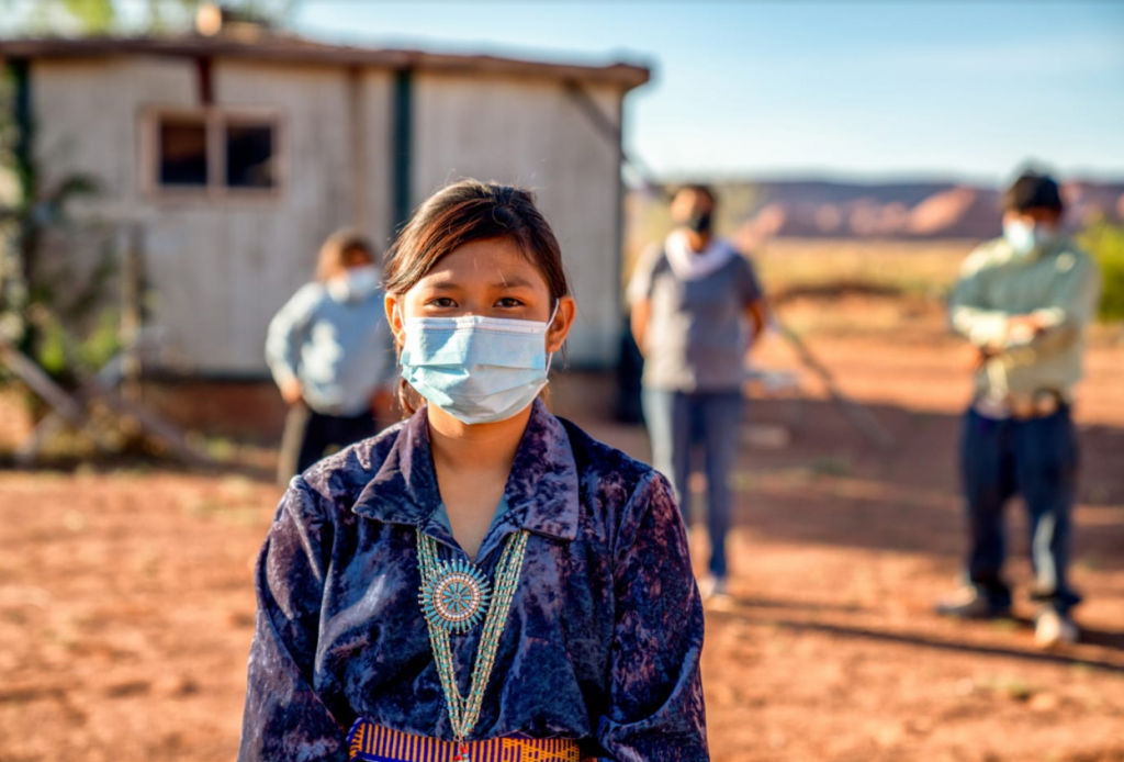 Young girl wearing Indigenous jewelry and accessories and a light blue disposable face mask on